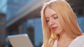 Mujer rubia bastante joven que usa el dispositivo de la tableta afuera en la calle Sonrisa de la mujer, golpeando ligeramente en  almacen de video