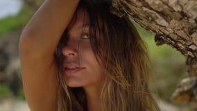 Mujer rubia bonita que presenta para un lanzamiento de la cámara en la playa salvaje almacen de video