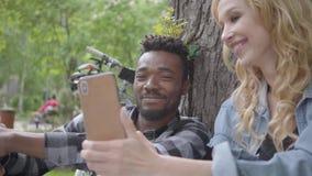 Mujer rubia bonita y hombre afroamericano hermoso que se sientan debajo de un ?rbol viejo en el parque La se?ora que muestra im?g metrajes