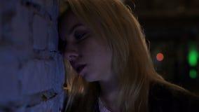 Mujer rubia borracha que coloca la pared cercana en el club de noche, sufriendo de resaca almacen de video