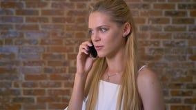 Mujer rubia caucásica linda joven que habla en un teléfono celular, pared de ladrillo en el fondo