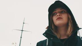 Mujer rubia caucásica soñolienta joven en casquillo y capilla negros delante del palo de la nave almacen de metraje de vídeo