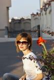 Mujer rubia cerca de una flor Imagen de archivo