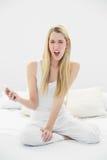 Mujer rubia chocada que sostiene su smartphone mientras que se sienta en su cama Imagenes de archivo