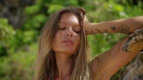 Mujer rubia con el pelo largo y tatuaje en la mano que presenta para la cámara almacen de video