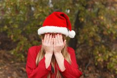 Mujer rubia con el sombrero de la Navidad que cubre su cara Imagenes de archivo