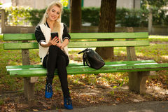 Mujer rubia con el teléfono elegante en un banco en parque Foto de archivo