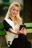 Mujer rubia con el teléfono elegante en un banco en parque Fotografía de archivo