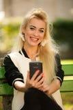 Mujer rubia con el teléfono elegante en un banco en parque Imagen de archivo