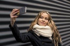 Mujer rubia con el teléfono móvil a disposición Imagen de archivo libre de regalías