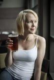 Mujer rubia con el vidrio de consumición hermoso de los ojos azules de cerveza clara Foto de archivo libre de regalías