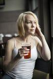 Mujer rubia con el vidrio de consumición hermoso de los ojos azules de cerveza clara Imagen de archivo libre de regalías