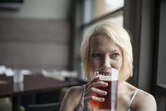 Mujer rubia con el vidrio de consumición hermoso de los ojos azules de cerveza clara Fotos de archivo