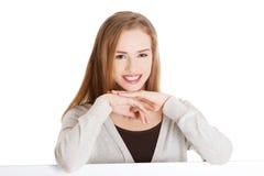 Mujer rubia con la mano en la barbilla que se sienta en el escritorio imagenes de archivo