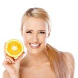 Mujer rubia con la sonrisa hermosa que celebra la naranja Foto de archivo libre de regalías