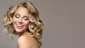 Mujer rubia con la sonrisa hermosa rizada del pelo imagen de archivo
