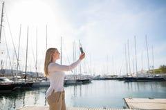 Mujer rubia con la tableta digital al aire libre Imágenes de archivo libres de regalías