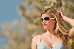 Mujer rubia con las gafas de sol bajo árbol floreciente Imagen de archivo libre de regalías