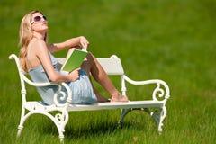 Mujer rubia con las gafas de sol que se sientan en el banco blanco Fotos de archivo