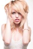 Mujer rubia con las manos en pelo Imagenes de archivo