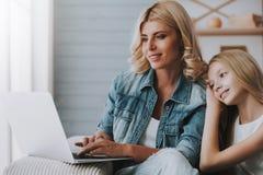 Mujer rubia con las páginas de Internet de la ojeada de la niña en el ordenador portátil Imagenes de archivo