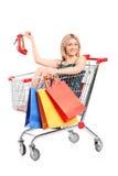Mujer rubia con los bolsos que presentan en un carro de compras Foto de archivo