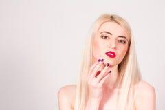 Mujer rubia con los labios rojos y con una manicura que toca su cara Manicura Fotos de archivo