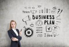 Mujer rubia con un marcador cerca de un bosquejo del plan empresarial en un concr Imagen de archivo