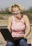 Mujer rubia con un ordenador portátil foto de archivo