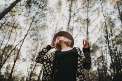 Mujer rubia con un sombrero que mira para arriba en el campo Forest Tr foto de archivo libre de regalías