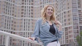 Mujer rubia confiada bonita en la chaqueta de los vaqueros que presenta delante del rascacielos, mirando lejos sonriente Forma de almacen de video