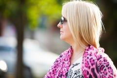 Mujer rubia confiada hermosa joven en gafas de sol y bufanda rosada del leopardo que camina en día de verano ventoso con mucha lu foto de archivo libre de regalías