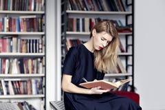 Mujer rubia de Causasian que lee un libro en una biblioteca pública Labios rojos, pelo blanco largo Fotografía de archivo libre de regalías