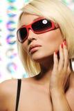 Mujer rubia de la belleza en gafas de sol rojas de la manera Imagen de archivo libre de regalías