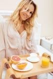 Mujer rubia de la belleza joven que desayuna en la mañana soleada temprana de la cama, sitio del interior de la casa de la prince Fotos de archivo libres de regalías