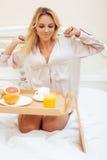 Mujer rubia de la belleza joven que desayuna en la mañana soleada temprana de la cama, sitio del interior de la casa de la prince Foto de archivo