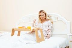Mujer rubia de la belleza joven que desayuna en la mañana soleada temprana de la cama, sitio del interior de la casa de la prince Foto de archivo libre de regalías