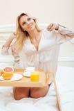 Mujer rubia de la belleza joven que desayuna en la mañana soleada temprana de la cama, sitio del interior de la casa de la prince Fotografía de archivo libre de regalías