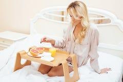 Mujer rubia de la belleza joven que desayuna en la mañana soleada temprana de la cama, sitio del interior de la casa de la prince Fotos de archivo