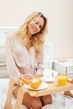 Mujer rubia de la belleza joven que desayuna en la mañana soleada temprana de la cama, sitio del interior de la casa de la prince Imagenes de archivo