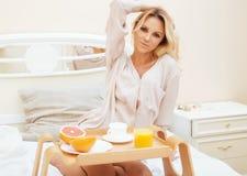 Mujer rubia de la belleza joven que desayuna en la mañana soleada temprana de la cama, sitio del interior de la casa de la prince Imagen de archivo