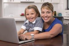 Mujer rubia de la madre así como sus años hermosos y dulces jovenes de la niña 6 a 8 que sientan en casa la cocina que goza con fotografía de archivo libre de regalías