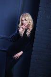 Mujer rubia de la muchacha hermosa en vestido de noche del negro del shikranom en un fondo oscuro Fotos de archivo