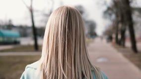 Mujer rubia de la visión trasera que camina y que mira a la izquierda Muchacha caucásica en capa azul con el pelo justo largo her metrajes