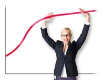 Mujer rubia de los busnes que empuja la línea del gráfico. Foto de archivo