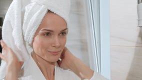Mujer rubia de mediana edad atractiva con la toalla blanca en su cabeza y en la albornoz que defiende en el cuarto de baño el esp almacen de video