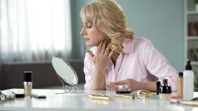 Mujer rubia de mediana edad que aplica maquillaje costoso en casa, cosméticos antienvejecedores fotografía de archivo libre de regalías