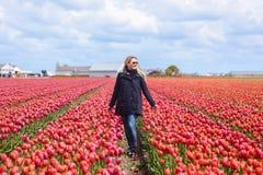 Mujer rubia de pelo largo hermosa soñadora que lleva la situación azul de la capa en un campo de tulipanes rosados imágenes de archivo libres de regalías
