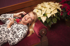 Mujer rubia de risa en silla púrpura usando el teléfono celular Fotos de archivo