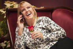 Mujer rubia de risa en silla púrpura usando el teléfono celular Imagen de archivo libre de regalías